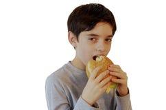 Menino que come um hamburguer e um sorriso Imagens de Stock
