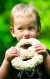 Menino que come um pretzel do chocolate Foto de Stock Royalty Free