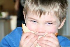 Menino que come um sanduíche Fotos de Stock Royalty Free