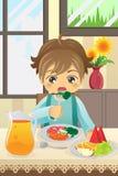 Menino que come vegetais Imagens de Stock Royalty Free
