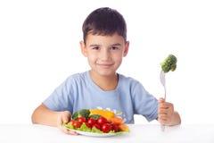 Menino que come vegetais Fotografia de Stock