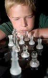Menino que concentra-se em seu movimento de xadrez seguinte Fotografia de Stock Royalty Free