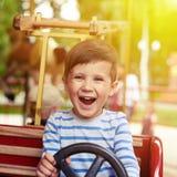 Menino que conduz um carro no carrossel Fotografia de Stock