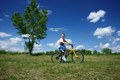 Menino que conduz uma bicicleta imagens de stock
