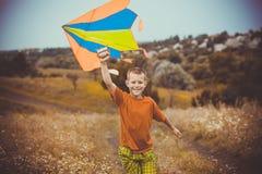 Menino que corre através do campo com o papagaio que voa sobre sua cabeça Fotografia de Stock