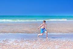 Menino que corre em uma praia Fotografia de Stock Royalty Free