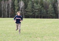 Menino que corre no prado Fotos de Stock Royalty Free
