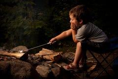 Menino que cozinha o marshmallow Fotografia de Stock Royalty Free