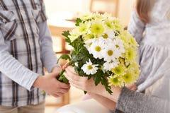 Menino que dá um grupo de flores fotos de stock royalty free