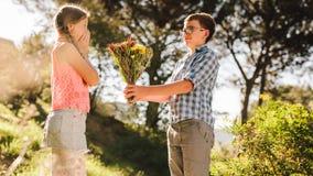 Menino que dá um ramalhete das flores a sua amiga em um parque imagens de stock