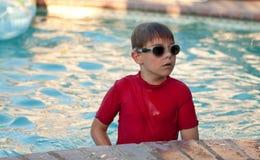 Menino que desgasta a camisa e óculos de proteção vermelhos na associação imagens de stock
