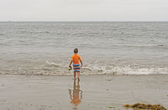 Menino que dirige para fora ao oceano Imagem de Stock
