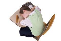 Menino que dorme na mesa da escola fotografia de stock