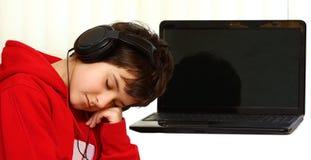 Menino que dorme por um portátil Fotos de Stock