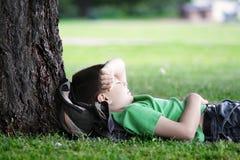 Menino que dorme sob a árvore Fotografia de Stock Royalty Free