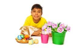 Menino que encontra-se e que abraça o coelho perto dos ovos orientais Fotografia de Stock Royalty Free