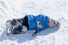 Menino que encontra-se na neve branca na roupa Na rua um o dia ensolarado O inverno, frio, geia a criança pequena de A caiu sobre Imagens de Stock Royalty Free