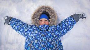 Menino que encontra-se na neve, com suas mãos acima Fotografia de Stock