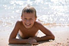 Menino que encontra-se na praia Fotografia de Stock Royalty Free