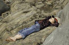 Menino que encontra-se na rocha na praia Fotografia de Stock