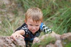 Menino que escala acima Boulder Fotografia de Stock