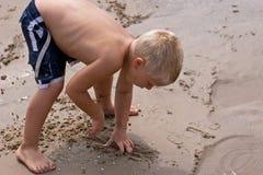 Menino que escava na praia Fotografia de Stock