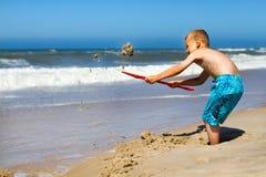 Menino que escava um furo na praia Fotografia de Stock Royalty Free