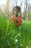 Menino que esconde atrás de um fistful da grama Foto de Stock Royalty Free