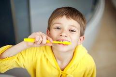 Menino que escova seus dentes na banheira, sorrindo Conceito saudável do estilo de vida imagens de stock