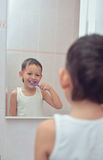 Menino que escova seus dentes na frente do espelho Imagem de Stock