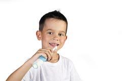 Menino que escova sua escova de dentes elétrica dos dentes Fotografia de Stock Royalty Free