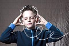 Menino que escuta fones de ouvido da garatuja da música e para apreciar imagem de stock