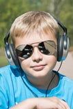 Menino que escuta a música através dos auscultadores Foto de Stock Royalty Free