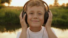 Menino que escuta a música através dos fones de ouvido na natureza sob o por do sol video estoque