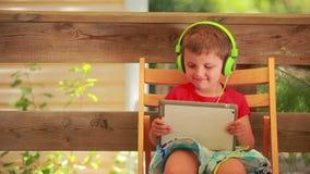 Menino que escuta a música em fones de ouvido verdes filme