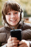 Menino que escuta a música em Smartphone Fotografia de Stock Royalty Free
