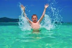 Menino que espirra a água no mar que olha a câmera Criança brincalhão 10 anos de lote cercado velho das gotas, mar cintilante bri Fotos de Stock Royalty Free