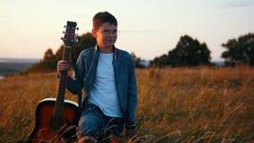 Menino que está com a guitarra de madeira no campo video estoque