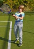Menino que está com raquete e bola de tênis na corte Imagens de Stock