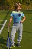 Menino que está com raquete e bola de tênis na corte Fotografia de Stock Royalty Free