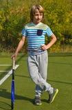 Menino que está com raquete e bola de tênis na corte Fotos de Stock Royalty Free