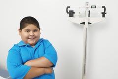 Menino que está pela escala de peso na clínica Foto de Stock Royalty Free
