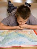 Menino que estuda um mapa Fotografia de Stock Royalty Free
