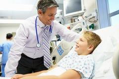 Menino que fala ao consultante masculino In Emergency Room imagens de stock