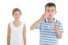 Menino que faz bolhas quando sua irmã que olha o imagem de stock