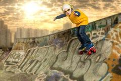 Menino que faz os truques em um skate, conluios no parque do patim O rapaz pequeno ao estilo do hip-hop imagens de stock royalty free