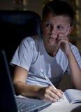 Menino que faz trabalhos de casa com portátil Fotografia de Stock Royalty Free