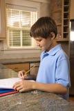 Menino que faz trabalhos de casa no contador de cozinha. imagem de stock
