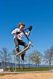 Menino que faz truques com seu 'trotinette' em um parque do patim Imagens de Stock Royalty Free