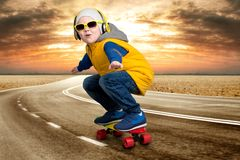 Menino que faz truques em um skate, patim na estrada O rapaz pequeno ao estilo do hip-hop imagens de stock